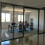 Floor-to-ceiling glass conference room walls with black aluminum framing