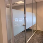 Glass office with sliding glass door and privacy opaque window film