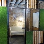 Wood block and green grass wall panels with swing glass door