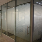 Glass offices with space saving frameless glass sliding doors