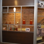 Office with sliding aluminum framed door and open shelf wall