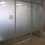 Sliding frameless glass door with matching privacy film