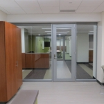 Centered glass office front with aluminum door frames and seamless glass