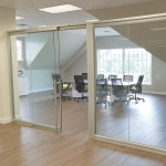 Freestanding View Series glass wall with self-closing sliding glass door