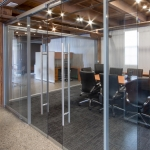 Glass conference room with double sliding glass doors, soft open/close door hardware