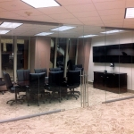 Double swing frameless glass doors on glass conference room walls