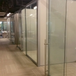 Freestanding glass wall system with locking sliding door pulls