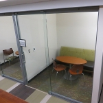 Full height sliding glass office doors in College University wall application
