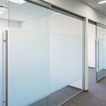 Glass office walls with soft-closing sliding glass door hardware