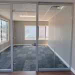 glass wall office with glass slab swing door