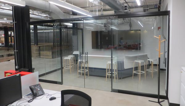Office space with glass partitions and interior frameless glass door