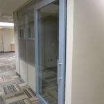 Aluminum framed sliding glass door office with designer 3form wall panels
