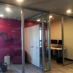 Glass offices with seamless glass return wall (wingback) and butt-joint clerestory