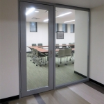 University conference/huddle room glass wall fronts with swing door glass insert